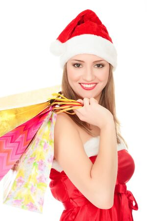Pretty girl in a red Christmas hat with colorful bags isolated over white background. Stock Photo - 8366967