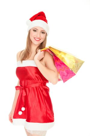 Pretty girl in a red Christmas hat with colorful bags isolated over white background. Stock Photo - 8366975