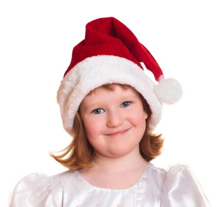 Portrait of pretty christmas girl in white dress and santa hat, smiling isolated on white background photo
