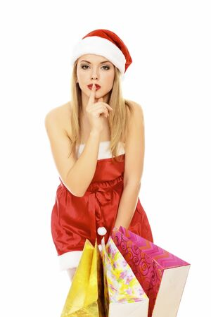 Pretty young woman dressed as Santa with shopping bags, isolated over a white background. photo