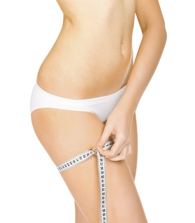 metric: Young tanned woman measuring her body, isolated on white background. Stock Photo