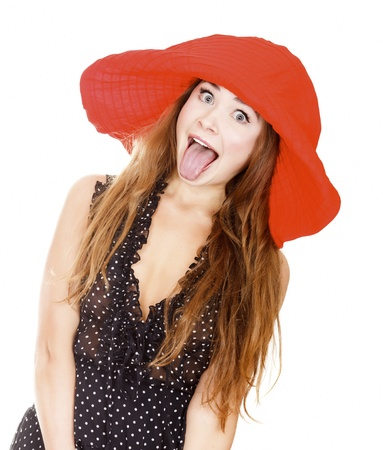 female tongue: Woman in red hat posing against white background and showing her tongue.
