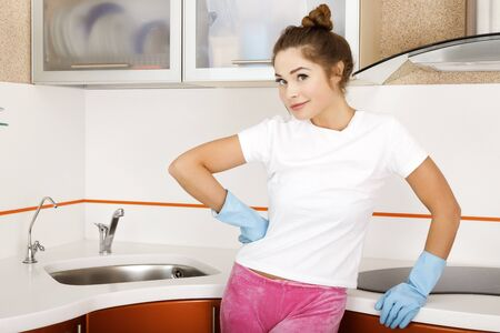 Young woman in blue rubber gloves in the kitchen photo