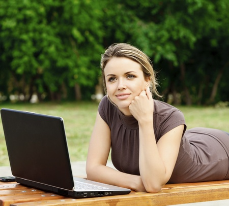 Young pretty woman with laptop lying on the bench at a park  photo