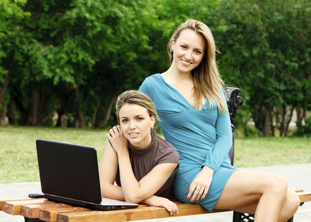 Two girlfriends on the bench with laptop at park photo