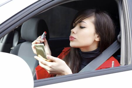 Pretty young woman in a car doing makeup.  photo