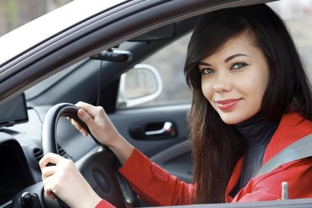 automobile dealers: Pretty brunette driving a car