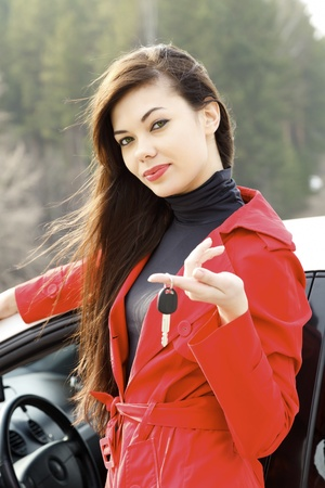 Beautiful young happy woman with car keys.