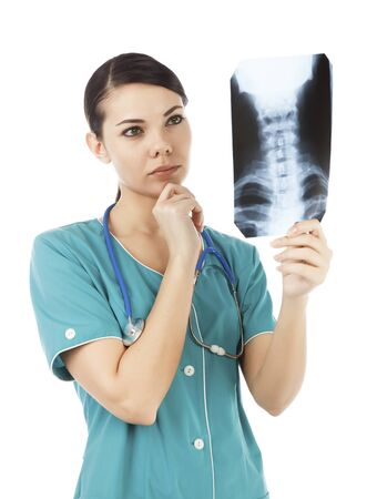 Thoughtful female doctor in the green uniform looking at the x-ray image photo