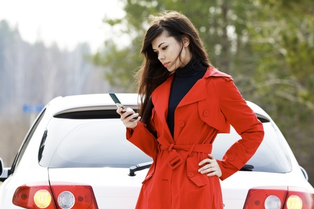 crash car: Young woman sending an sms to the car service.