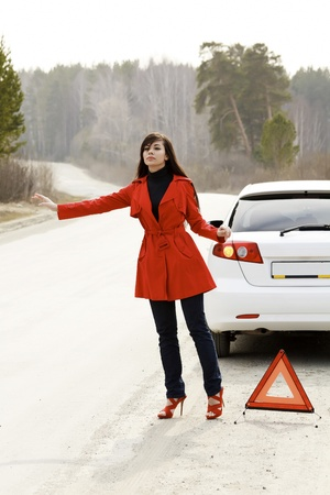 Young woman standing by the red triangle sign and her damaged car
