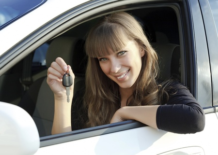 Beautiful young happy woman with car key.  photo