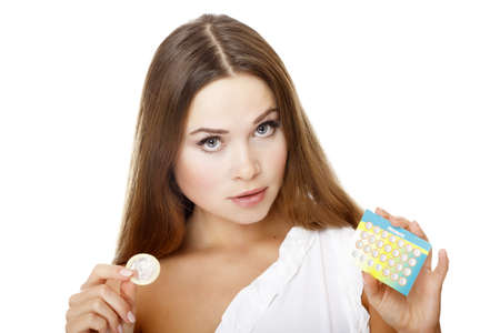 contraceptive: Pretty girl with condom and contraceptive pills. Isolated over a white background.