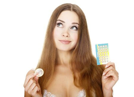 Pretty girl with condom and contraceptive pills. Isolated over a white background.  photo