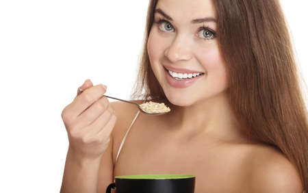 portrait of young caucasian woman eating cereals, isolated over white background.  photo