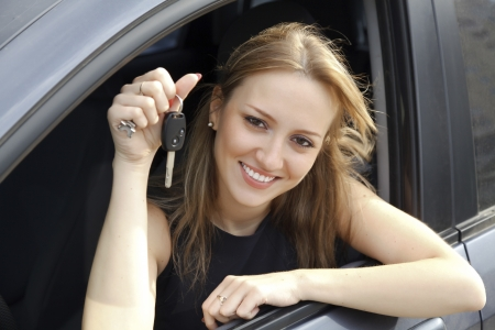 car dealer: The happy woman showing the key of her new car