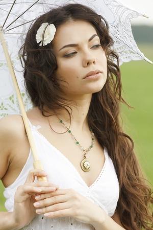 Pretty girl with white umbrella photo
