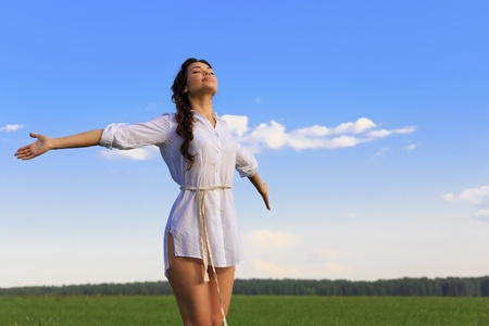 day dreaming: Young happy woman in green field, evening light Stock Photo