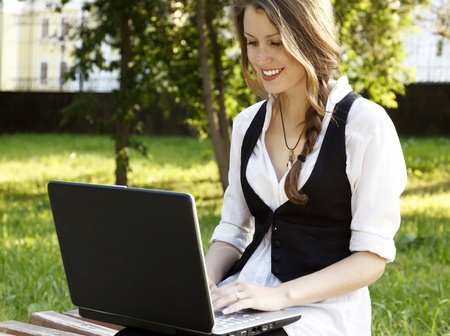 Young pretty woman with laptop sitting on the bench in a park Stock Photo - 9967046