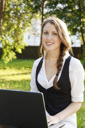 Young pretty woman with laptop sitting on the bench in a park Stock Photo - 9967223