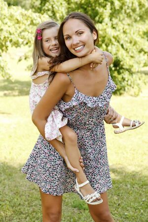 mother giving daughter piggy back ride at summer park.  photo