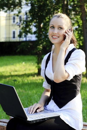 Young pretty woman with laptop sitting on the bench in a park. Stock Photo - 9967242