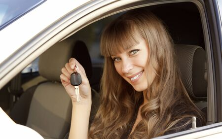 Cheerful young lady sitting in a car and showing the key  Stock Photo