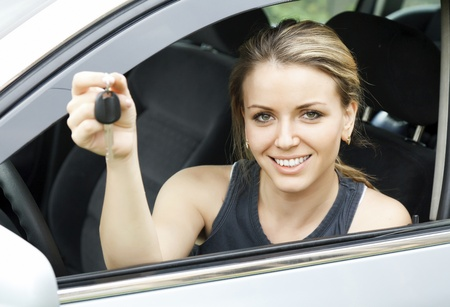 Beautiful young happy woman in car showing the keys  photo