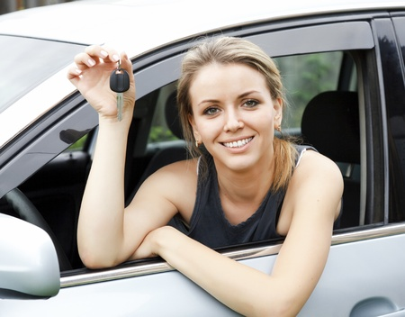 Beautiful young happy woman in car showing the keys Stock Photo - 9967271