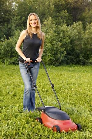 gras maaien: vrouw maaien met grasmaaier Stockfoto