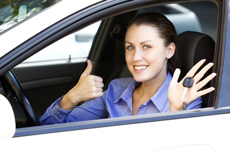 Pretty female driver in a white car showing the car key  photo