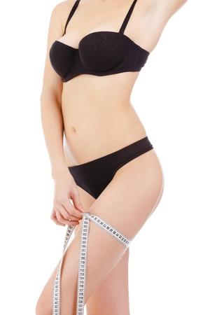 cintas metricas: La mujer mide su muslo, aislados en fondo blanco