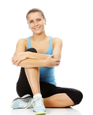 young brunette woman wearing sports clothes sitting on a white floor, isolated against white background  photo