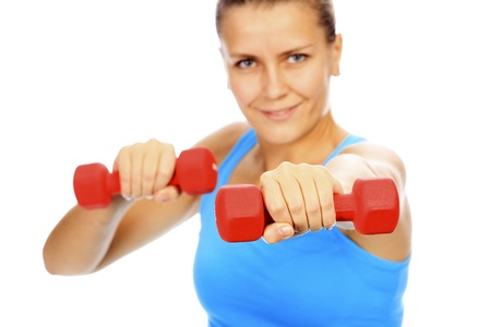 Smiling woman with barbells, focus is on the nearest barbell, shallow depth of view.
