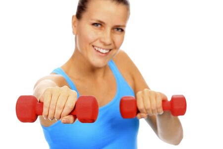 Smiling woman with barbells, focus is on the nearest barbell, shallow depth of view. Stock Photo - 11741474
