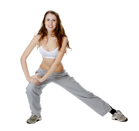 Beautiful young woman makes stretching excersize, isolated over white background Stock Photo - 11940348