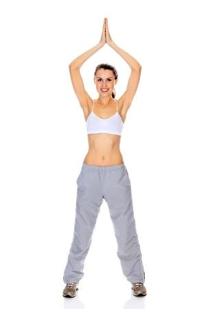 Smiling girl doing yoga excercise standing on white floor Stock Photo - 11960614