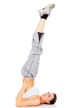 Portrait of healthy girl doing a yoga pose with feet in the air  photo