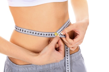 cropped image: Cropped image of a fit young woman measuring her waistline  Stock Photo