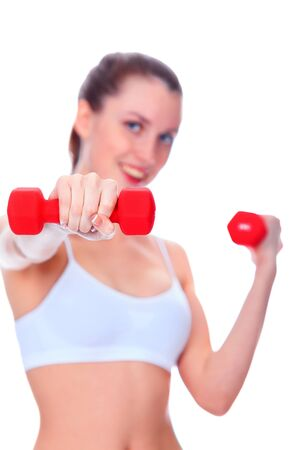 Smiling woman with barbells, focus is on the nearest barbell, shallow depth of view photo