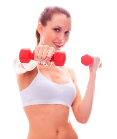 Smiling woman with barbells, focus is on the nearest barbell, shallow depth of view.  photo