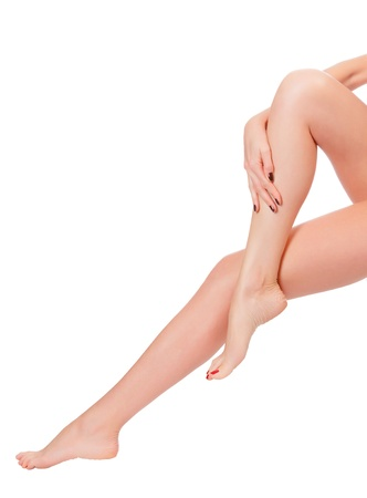 care for beautiful woman body. Perfect long female legs against white background, no shadow photo