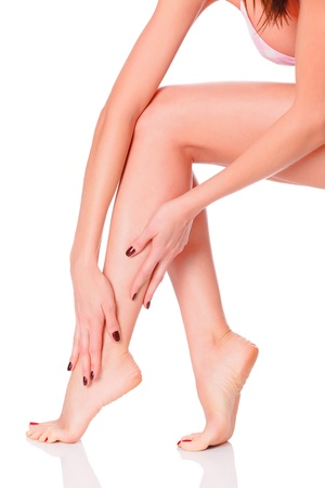After depilation.  Perfect long female legs against white background photo