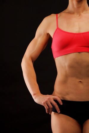 Female fitness bodybuilder posing against black background photo