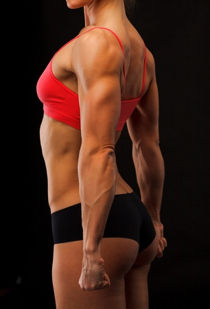 Female fitness bodybuilder posing against black background Stock Photo - 12498951