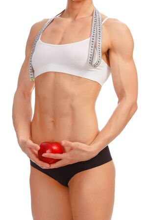 Muscular woman with apple and tape measure posing against white background Stock Photo - 12498821