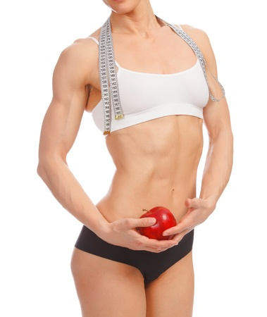 athletic body: Muscular woman with apple and tape measure posing against white background