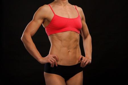 bodybuilder training: Female fitness bodybuilder posing against black background  Stock Photo