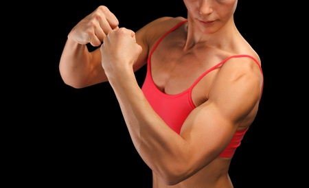 bicep: Female fitness bodybuilder posing against black background  Stock Photo