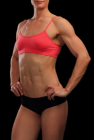 female bodybuilder: Female fitness bodybuilder posing against black background  Stock Photo